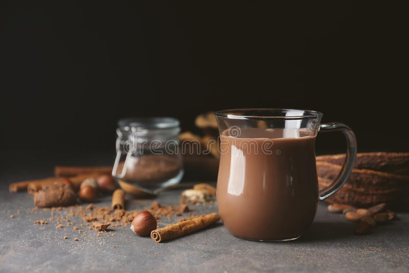 Cup with hot cocoa drink and cinnamon on table against dark background royalty free stock images