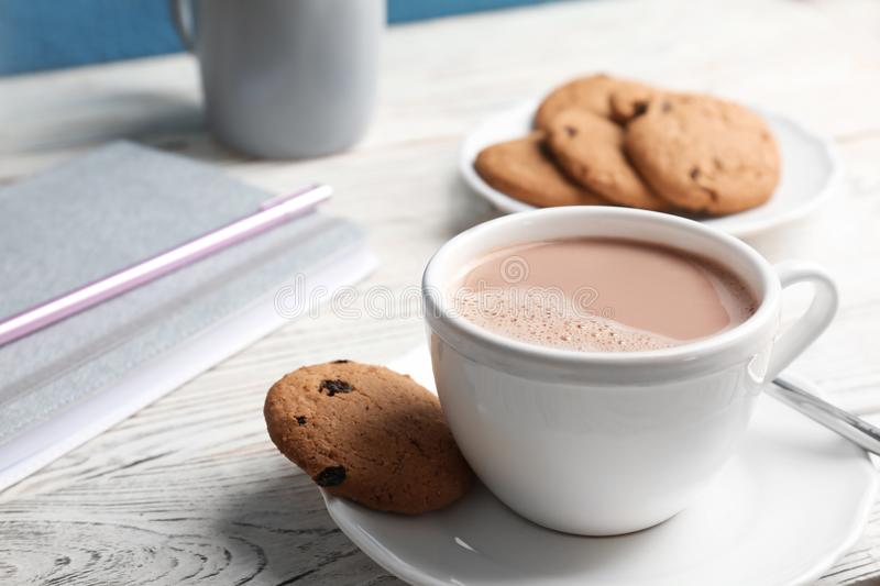 Cup with hot cocoa drink and cookie stock image