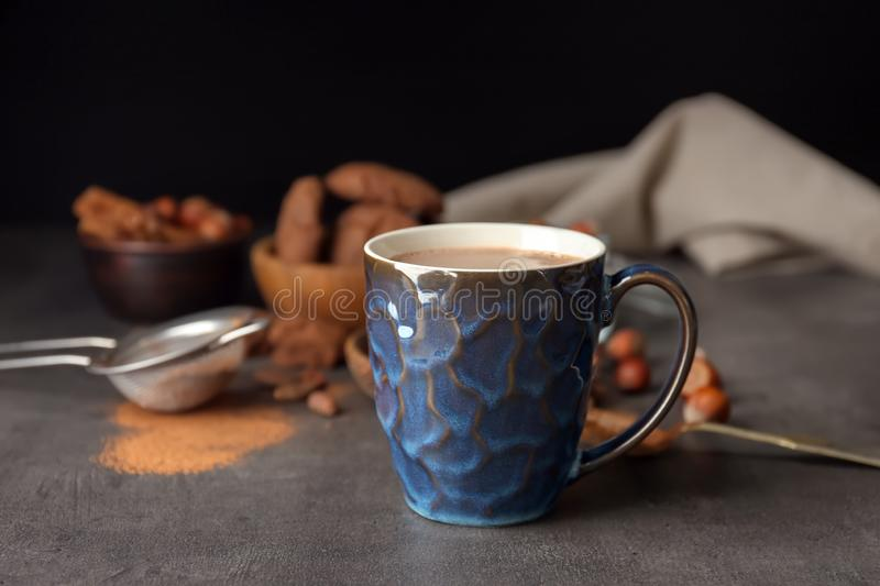 Cup with hot cocoa drink on table against dark background stock photos