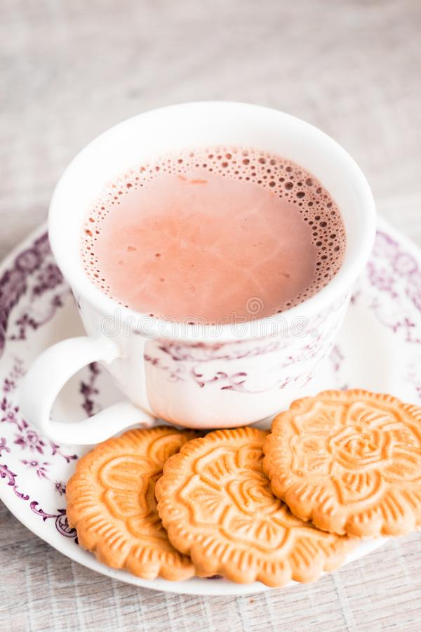 Cup of hot cocoa drink with vanilla flower shaped cookies on a dessert plate on a wooden table, selective focus. Food for breakfas. T. Christmas food royalty free stock images