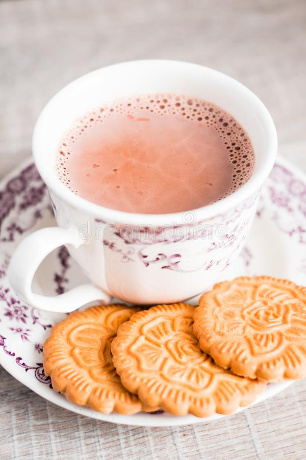 Cup of hot cocoa drink with vanilla flower shaped cookies on a dessert plate on a wooden table, selective focus. Food for breakfas. T. Christmas food stock photo