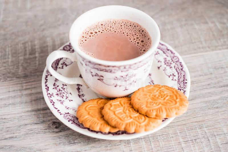 Cup of hot cocoa drink with vanilla flower shaped cookies on a dessert plate on a wooden table, selective focus. Food for breakfas. T. Christmas food stock images