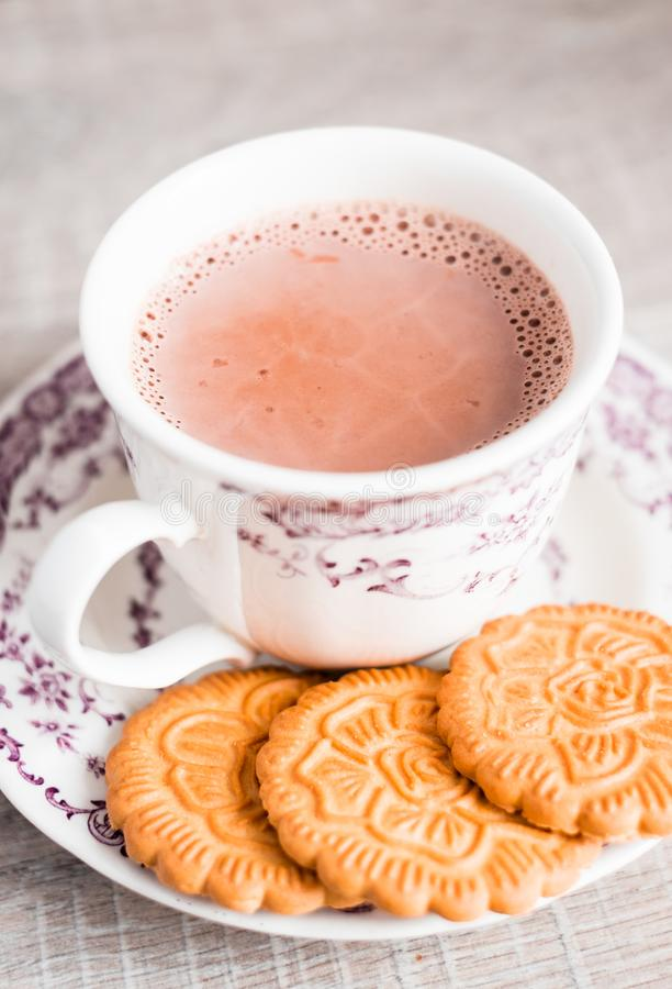 Cup of hot cocoa drink with vanilla flower shaped cookies on a dessert plate on a wooden table, selective focus. Food for breakfas. T. Christmas food royalty free stock photo
