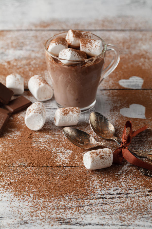 cup of hot cocoa with marshmallows, cinnamon and chocolate on wooden background stock photography