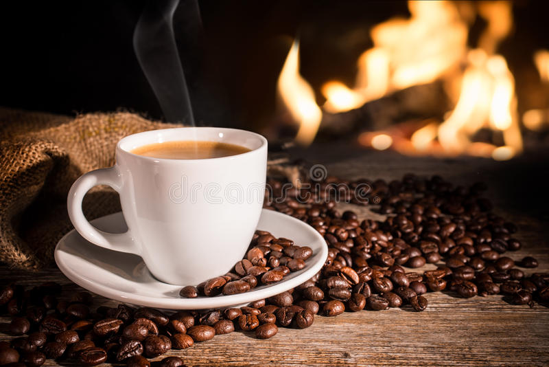 Cup of hot coffee. And coffee beans near fireplace stock image
