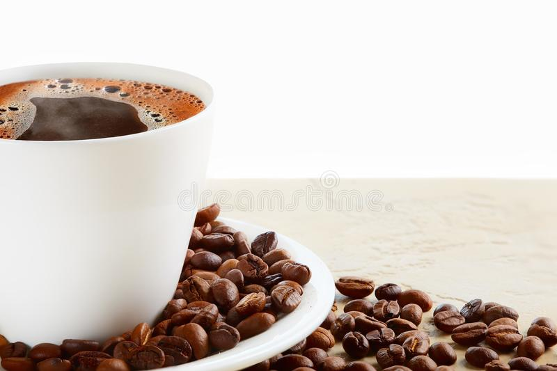 A cup of hot coffee with coffee beans on a white background stock images