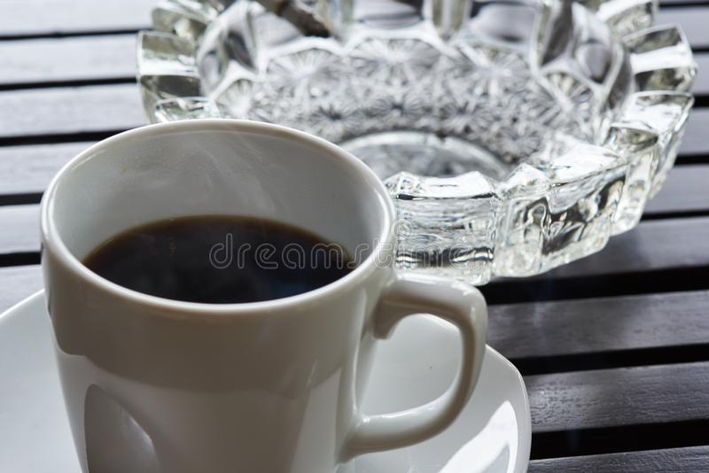 A cup of hot coffee and cigarette ashtray on the table stock photo