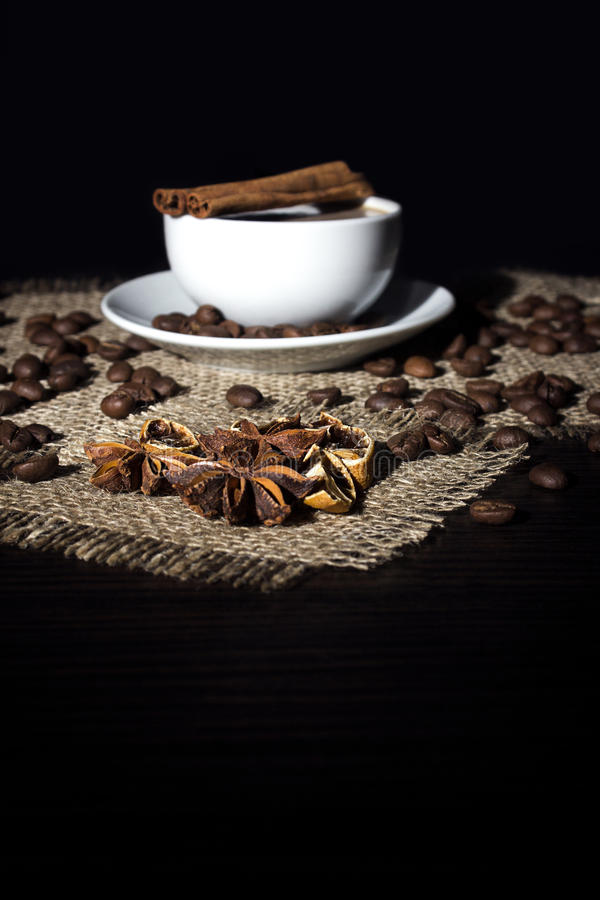 Cup of hot coffee, cinnamon, star anise,lemon and coffee beans royalty free stock image