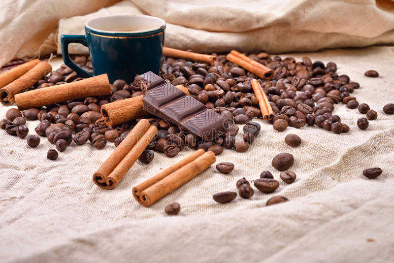 cup of hot coffee with cinnamon sticks bitten bar of