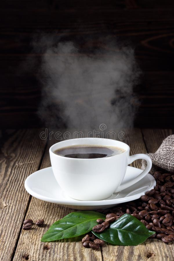 Cup of hot coffee with coffee beans and leaf stock image