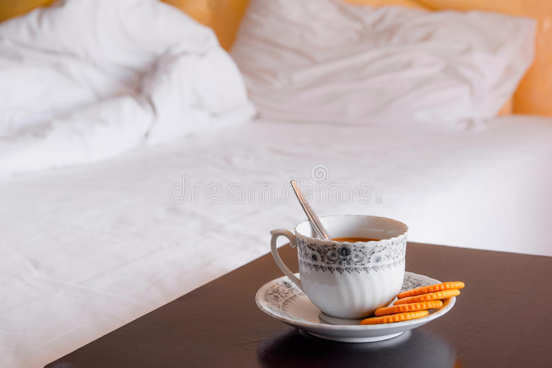 Cup of hot coffee with cookie. In morning time on blurred bed stock images
