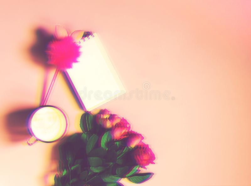 The cup of hot coffee, empty notepad with funny pen and bouquet of fresh roses on soft pink background. Glitch effect image royalty free stock image