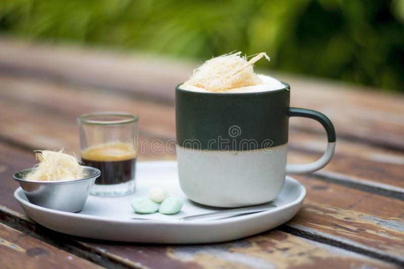 A cup of Hot Coffee with extra shot, sugar cotton candy and with thai traditional snacks on white plate stock photography