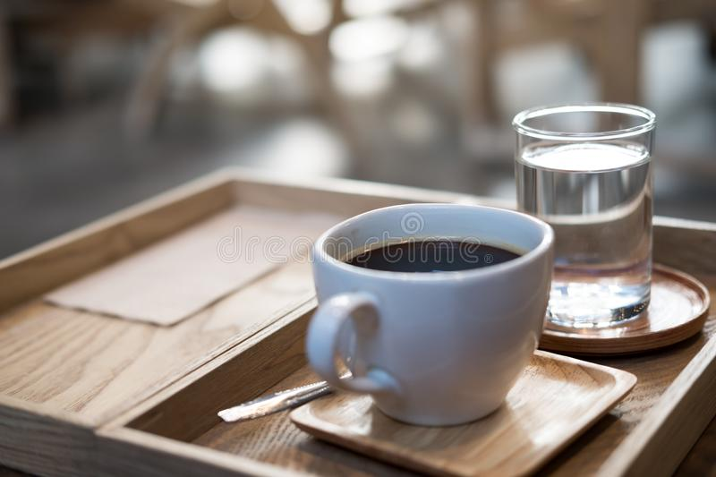 A cup of hot coffee and a glass of water in vintage wooden tray on the table in cafe. Closeup image of a cup of hot coffee and a glass of water in vintage wooden stock photos