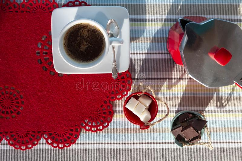 Cup of hot coffee, Italian coffee maker, moka pot coffee, sugar bowl and chocolate on blue red kitchen table in sunny morning, top stock image