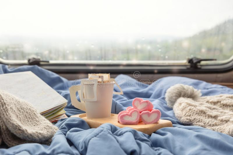 A cup of hot coffee with marshmallow near the window in the caravan camping car stock photos