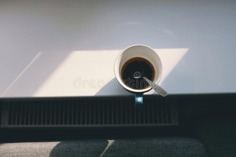 A cup of hot coffee in the morning on window sill of high building.  royalty free stock image