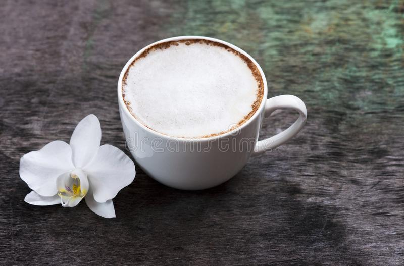 A cup of hot coffee and orchid flower on the wooden background. Traditional drink cappuccino or cocoa Wooden background Orchid flo royalty free stock photos