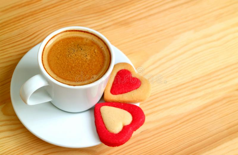 Cup of hot coffee with a pair of heart shaped cookies on wooden table royalty free stock photography