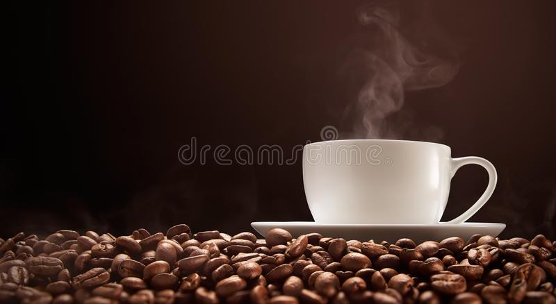 Cup of hot coffee with smoke on coffee beans royalty free stock photo