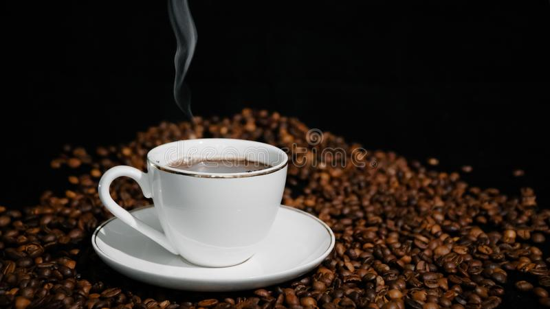 Cup with hot coffee and steam on a dark background.  royalty free stock images