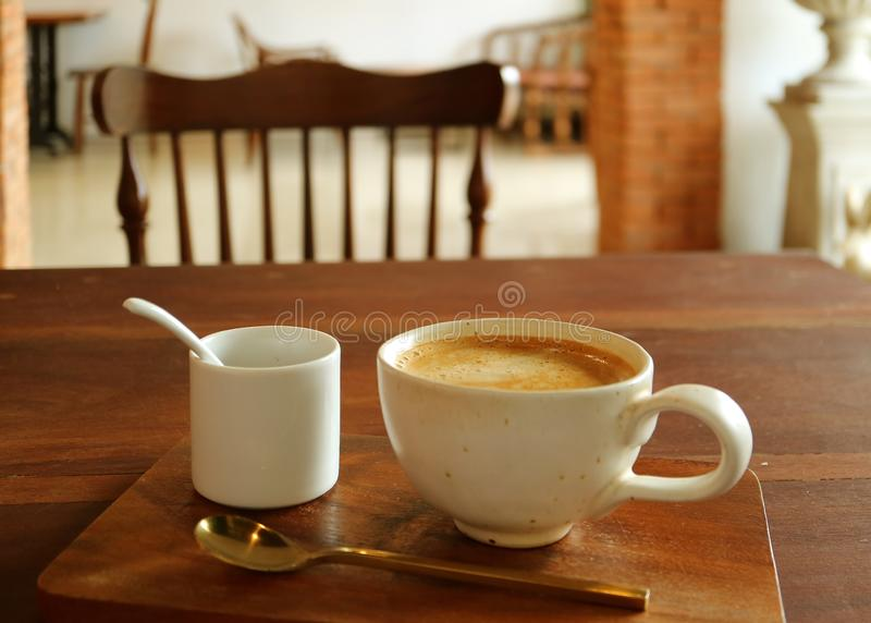 A cup of hot coffee with sugar pot and brass teaspoon served on wooden table in the dining room royalty free stock photos