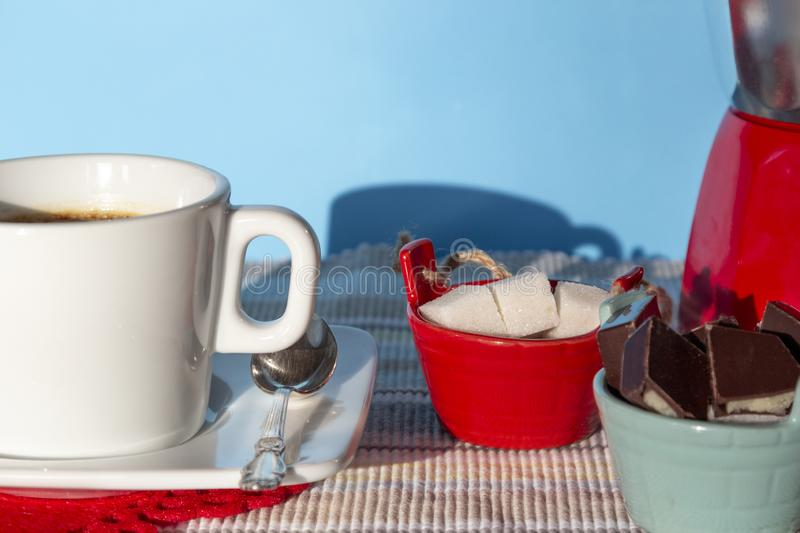 Cup of hot coffee/tea with sugar bowl and chocolate on blue background in sunny morning stock photo