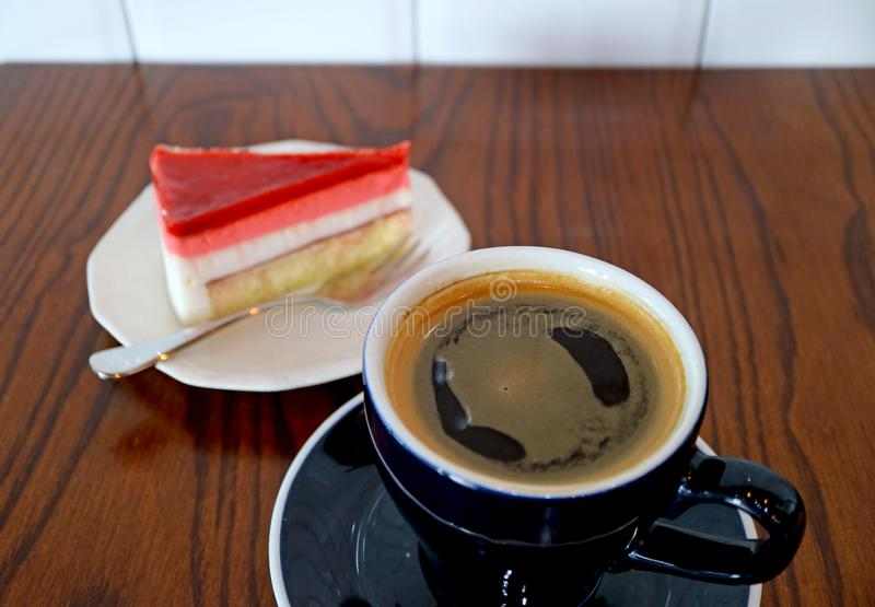 Cup of Hot Coffee on Wooden Table with a Slice of Raspberry Mousse Cake in Background stock photo