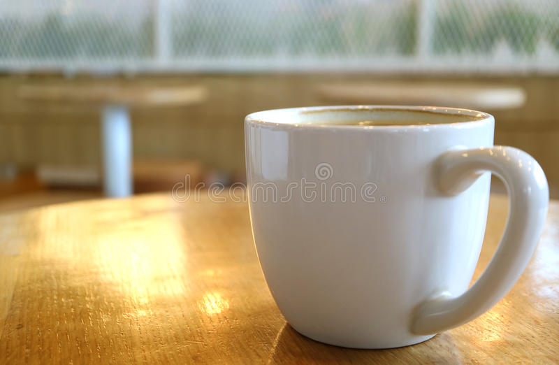 Cup of Hot Coffee on a Wooden Table with Sunlight Reflections royalty free stock photos