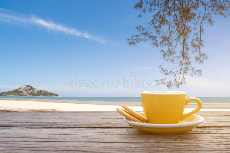 A cup of hot espresso coffee mugs placed on a wooden floor on sea view with sunlight background,coffee morning royalty free stock photography