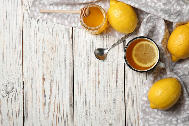 Cup with hot lemon tea and honey on wooden background, top view stock photos