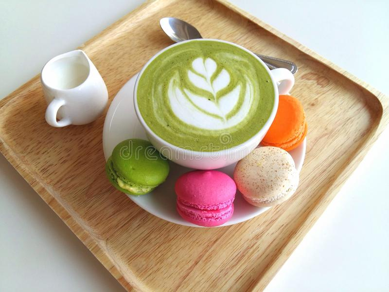 A cup of hot matcha latte so delicious with macaroon on wood royalty free stock photography