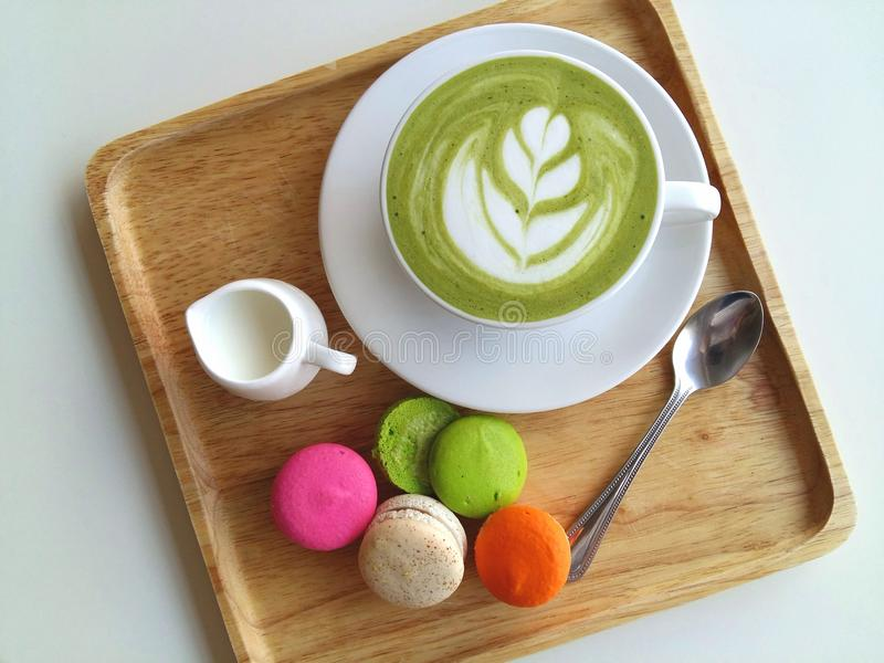 A cup of hot matcha latte so delicious with macaroon on wood stock photo
