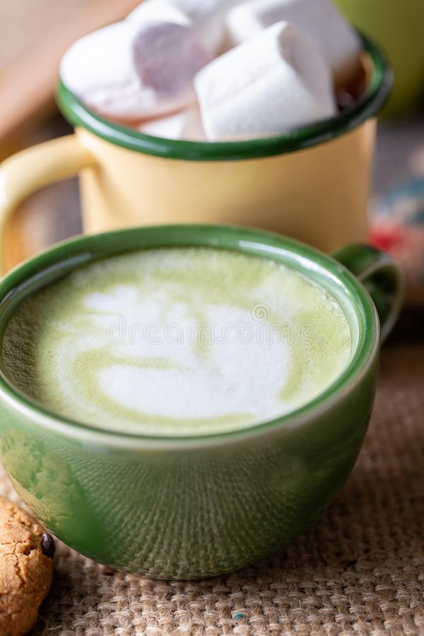 A cup of hot matcha latte on wooden floor stock photography