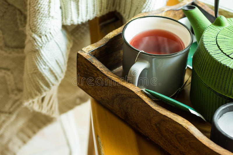 Cup of hot red fruit tea, green pot in tray, candle, knitted sweater hanging on wooden chair, cozy autumn, fall stock images