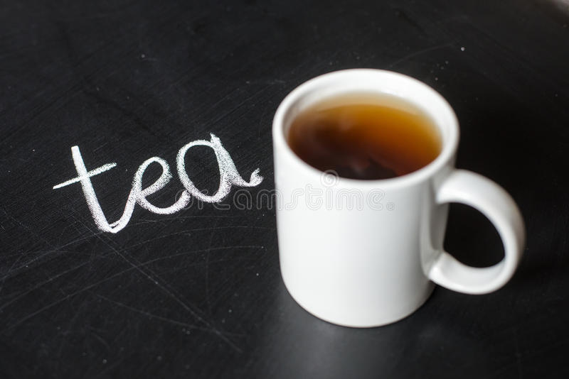 Cup of hot tea on a black board and text tea stock image