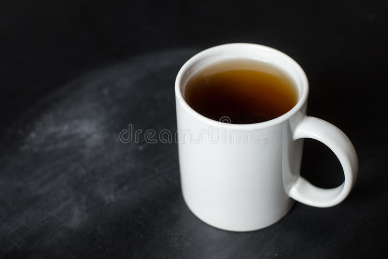 Cup of hot tea on a black board stock photos