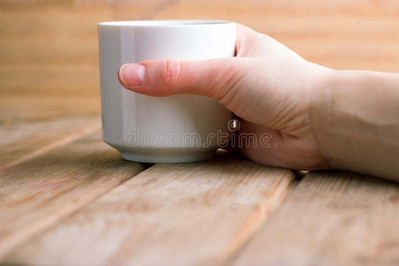 Cup of hot tea or coffee in hands royalty free stock image