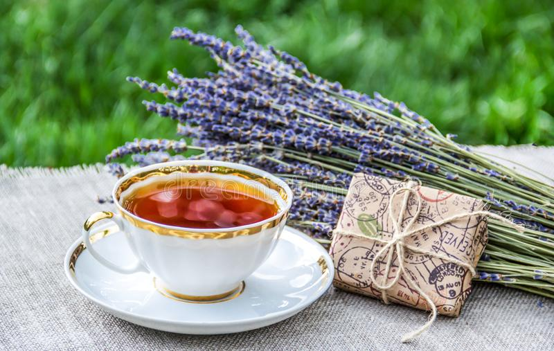 Cup of hot tea, fragrant lavender and gift. Summer tea in the garden. stock photography