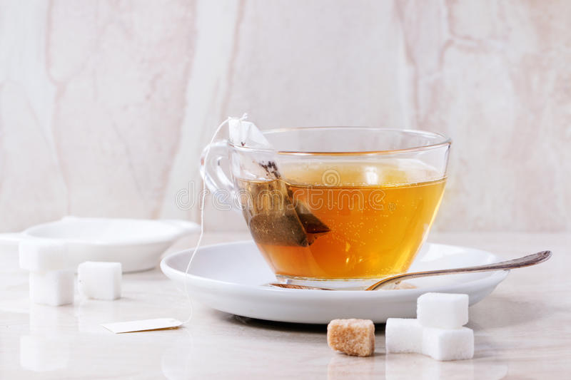 Cup of hot tea. Glass cup of hot tea on saucer with sugar cubes, spoon and tea bag over white marble backgtound. Top view stock photos