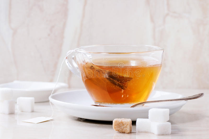 Cup of hot tea. Glass cup of hot tea on saucer with sugar cubes, spoon and tea bag over white marble backgtound. Top view stock image