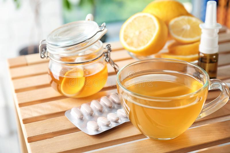 Cup with hot tea, honey and pills for cold stock photography
