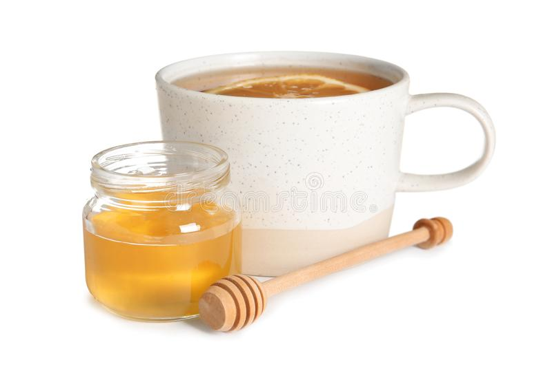 Cup of hot tea with lemon and honey jar. On white background royalty free stock images