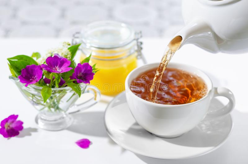 Cup of hot tea with mint and honey on white background. The process of pouring tea. Selective focus stock photos
