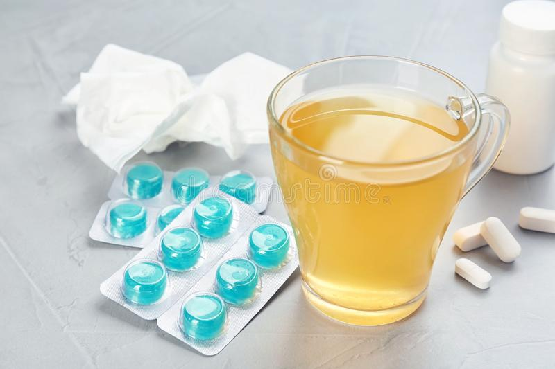 Cup with hot tea, pills and drugs for cold stock photos