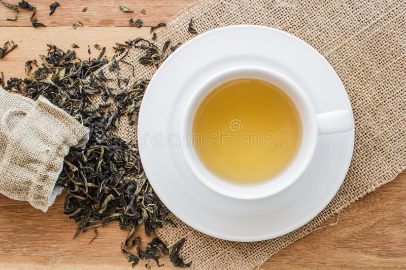 Cup of hot tea on sackcloth with dried tea leaves overflow form bag. On wooden table with copy space from top view. Time to relax with hot tea in morning stock photos