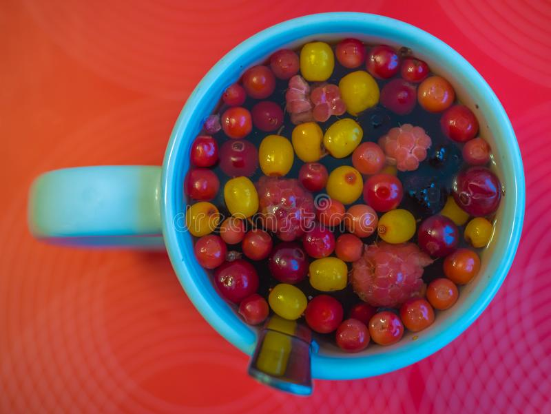 A Cup of hot tea with sea buckthorn berries, blueberries, raspberries and cranberries. healthy drink. cold treatment, vitamin tea. A Cup of hot tea with sea stock photo