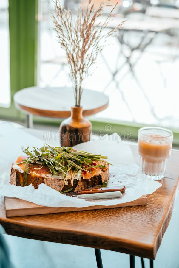 Cup of ice latte and toast. Cup of beautiful cold ice latte and toast with prosciutto and ruccola with wooden vase distichlis spicata on the wooden table. Cafe stock photo