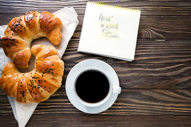 A cup of instant coffee with a croissant and message have a good time on the textured wooden background top view, cozy and royalty free stock image