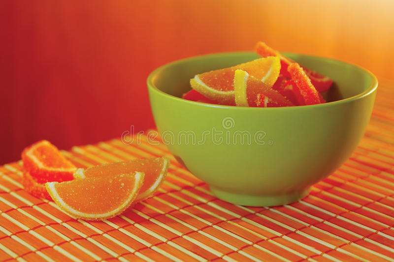 Cup with jelly sweet on a bamboo table cloth royalty free stock photo